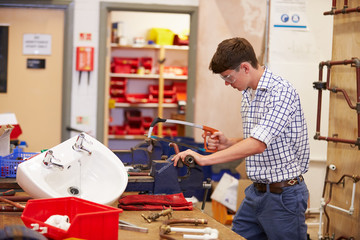 College Students Studying Plumbing Working At Bench