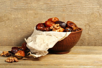 Tasty dates fruits in bowl, on wooden background
