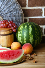 Composition of ripe watermelon, fruits and wooden barrel