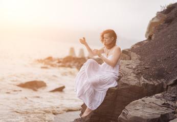 Portrait of redhead woman holding zen stones in hand.
