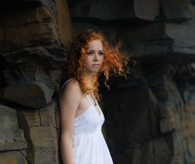 Beautiful redhead woman in a white dress, outdoor.