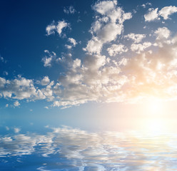 Sky with clouds and sun reflected in water surface.