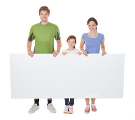 Family In Sportswear Holding Blank Billboard
