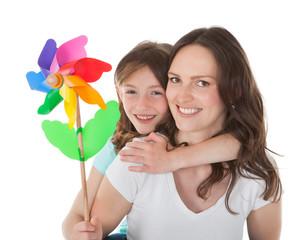 Happy Mother Piggybacking Daughter Holding Pinwheel