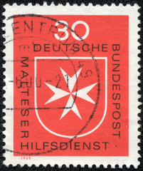 stamp printed in Germany, shows Maltese cross