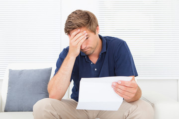 Stressed Man Holding Bill At Home
