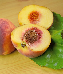 peach fruit cut, open on wooden background with leaf