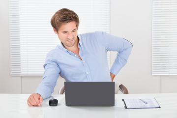 Businessman Suffering From Backache While Working On Laptop