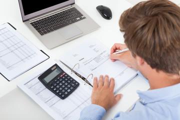 Businessman Calculating Tax At Desk