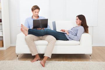 Couple Using Laptops On Sofa