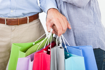 Couple's Hands Holding Multicolored Shopping Bags