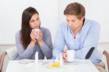 Sick Couple Drinking Lemon Tea At Table