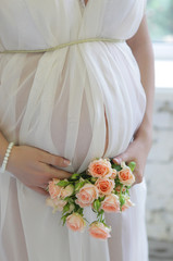 Closeup on tummy of pregnant woman, wearing long white dress, ho
