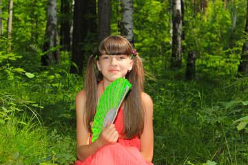Девочка сидит в лесу с веером