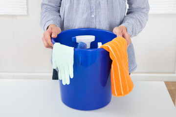 Woman With Cleaning Equipment In Bucket At Table