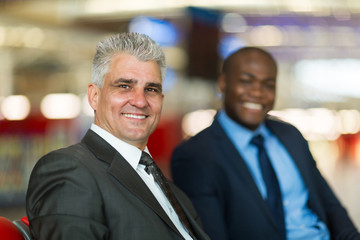 middle aged businessman and colleague at airport