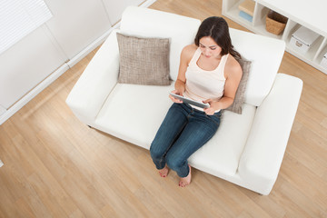Young Woman Using Digital Tablet On Sofa