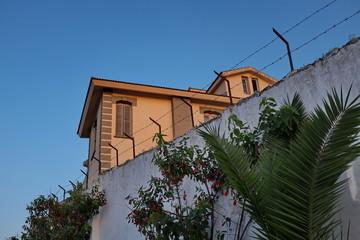 Villa entourée d'un mur avec barbelés.