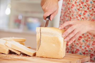Close Up Of Woman Slicing Loaf Of Bread In Kitchen