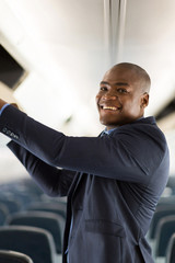 african businessman putting luggage into overhead locker on airp