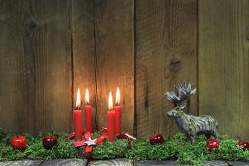 Advent: Kranz mit vier brennenden Kerzen und Holz im Hintergrund