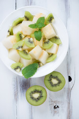 Fruit salad with melon and kiwi slices, view from above