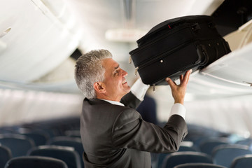 mature businessman putting luggage into overhead locker on airpl