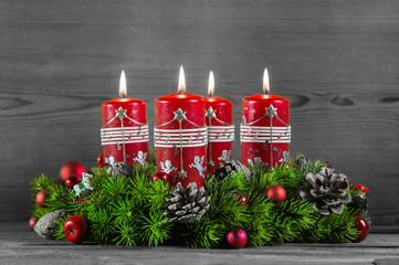 Adventskranz: vier rote brennende Kerzen auf Holz