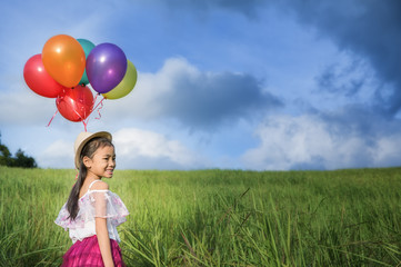 young asia girl holds tightly to a large bunch of helium filled