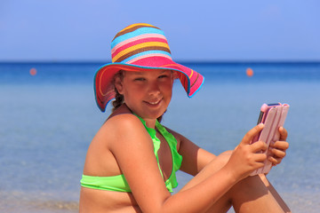Girl with tablet on the beach
