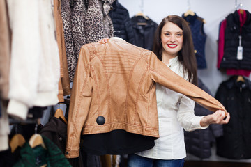 Cute young woman choosing jacket at clothing store