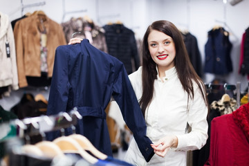 woman choosing jacket at boutique