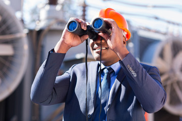 african electrician engineer using binoculars