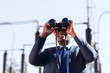 african american electrical manager using binoculars