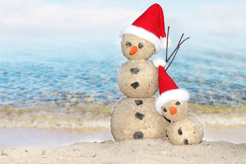 Two Snowmen at sea beach in santa hats