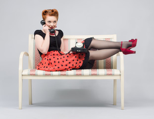 Woman talking on retro phone lying on a sofa.