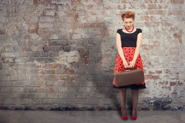 Beautiful woman with a suitcase in a retro style