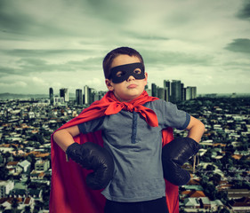 Child superhero modern city background.