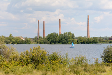 Industrial landscape with sailing boat on lake