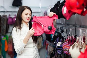Smiling woman choosing bra at store