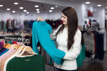 woman choosing sweater at clothing shop