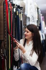 Woman choosing strap at shop