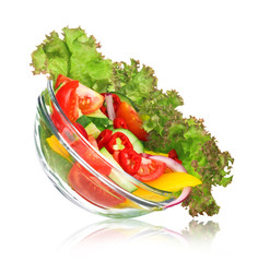 Delicious salad in the bowl in flight, isolated on white