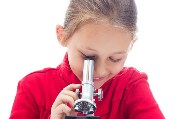 schoolgirl looks through a microscope on a white background isol