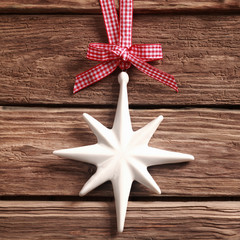 White Christmas star ornament on rustic wood
