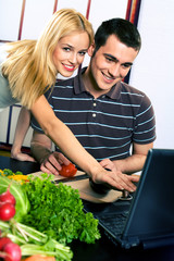 Young happy couple cooking at kitchen with laptop