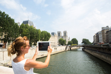 Young woman taking picture using digital tablet in Paris