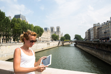 Woman using digital tablet outdoors, Paris