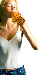 Young attractive blond woman drinking apple juice