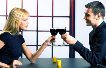 Young attractive happy smiling couple celebrating with red wine,